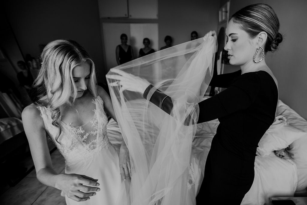 Bridesmaid in elegant black dress assisting beautiful bride into tulle wedding dress by Hanrie Lues