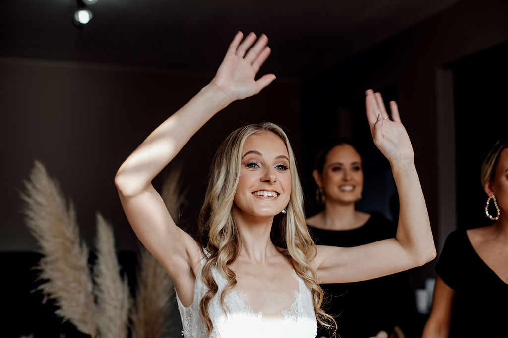 Bride with beautiful blonde curls smiling and waving at family members