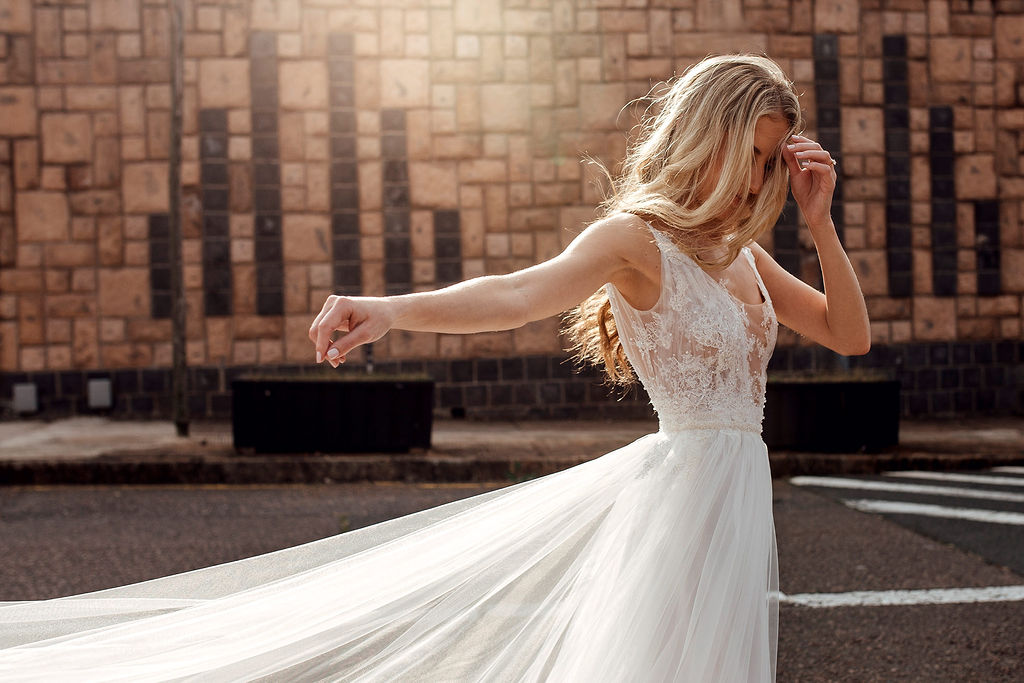 Bohemian bride in Hanrie Lues gown allows tulle dress to flow in the wind whilst bathed in soft warm sunlight