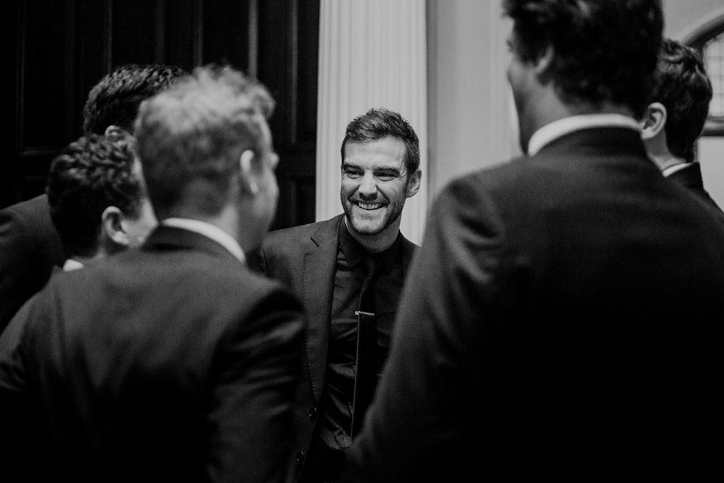Black and white documentary style image of groom laughing with groomsmen whilst waiting for wedding ceremony to begin