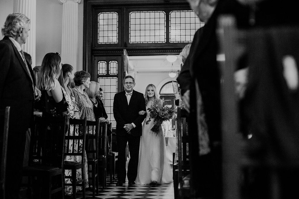 Black and white image of father walking beautiful bride down the aisle in trendy wedding at Durban Manor Hotel