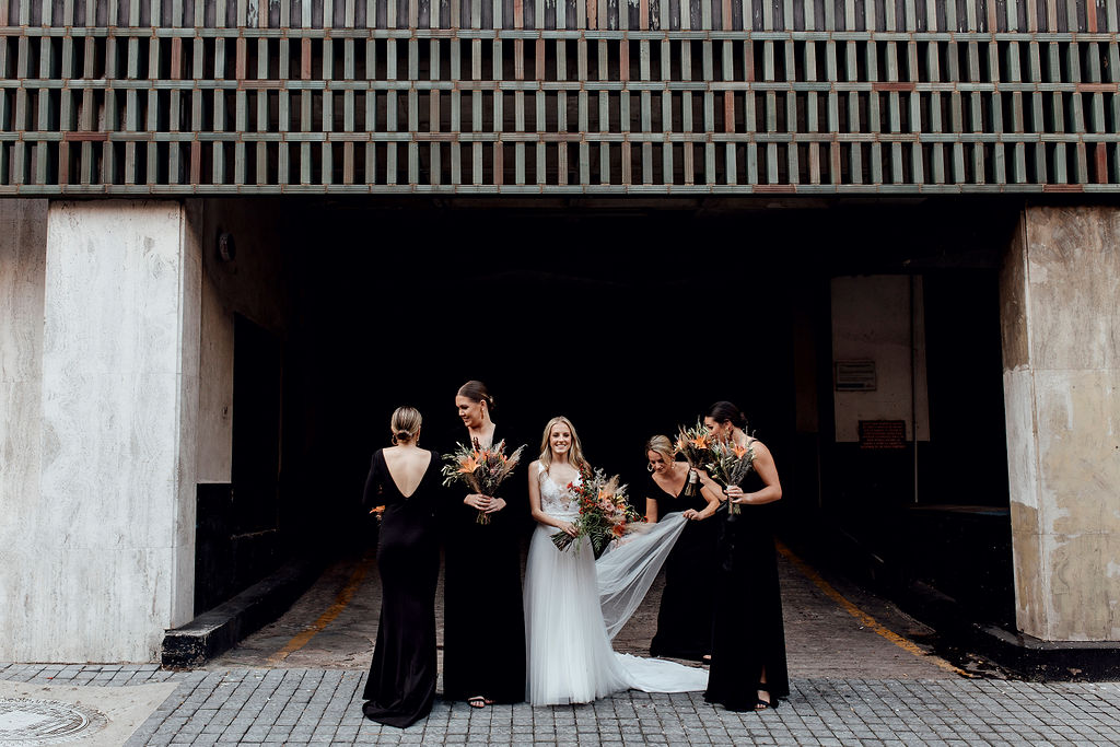 Elegant bride smiles at camera whilst trendy bridesmaids in black dresses fix her dress and get ready for photograph in urban setting