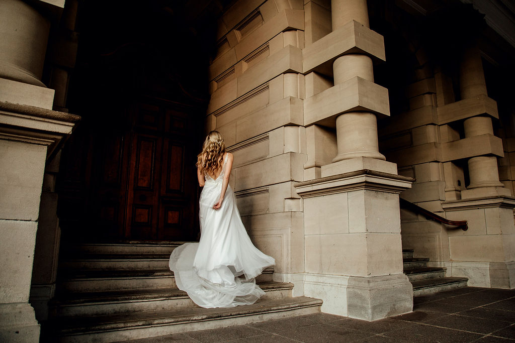 Contemporary bride spins and twirls her tulle wedding dress on the stairs of Durban city hall