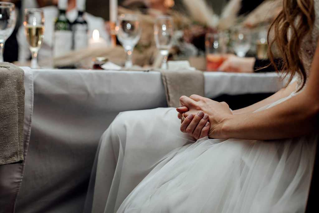 Close up image of modern bride's hands and new wedding ring during wedding reception
