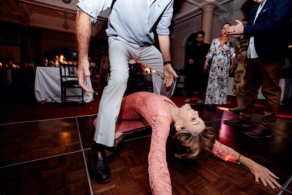 Mother of the groom bending backwards on wedding dancefloor whilst male wedding guests tries to pick her up off the floor