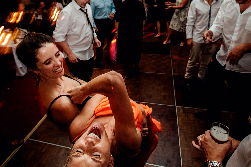 Wedding photograph of dancefloor action whilst two girls dance and laugh together