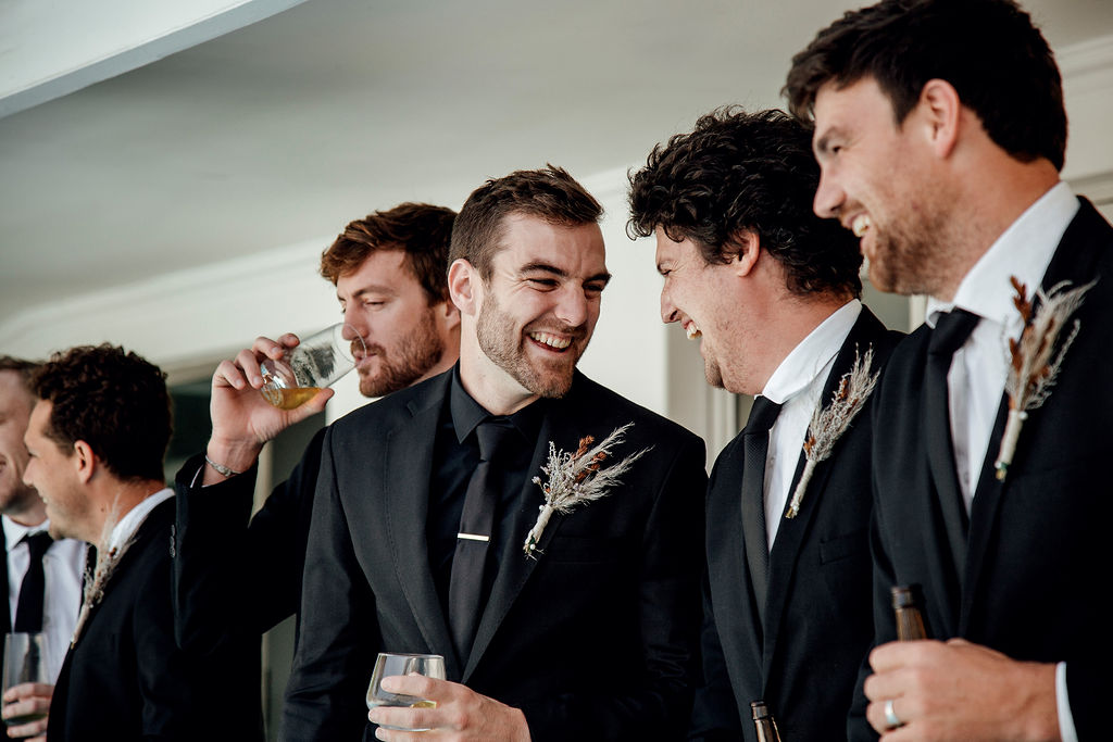 Handsome groom laughing together with groomsmen whilst sipping on whiskey