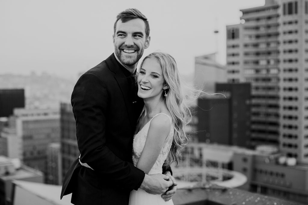 Black and white wedding image of happy newly weds holding each other and laughing on top of Durban city centre rooftop with city building as backdrop