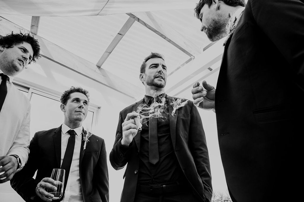 Trendy black and white photo of groom sharing cigar with groomsmen on wedding morning