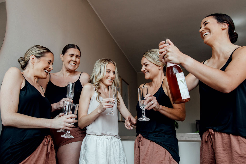 Matching bridesmaids giggling and popping open champagne on wedding morning
