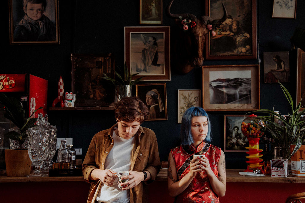 Alternative couple stand side-by-side in trendy coffee shop holding cups of coffee during couple shoot, girl has blue hair
