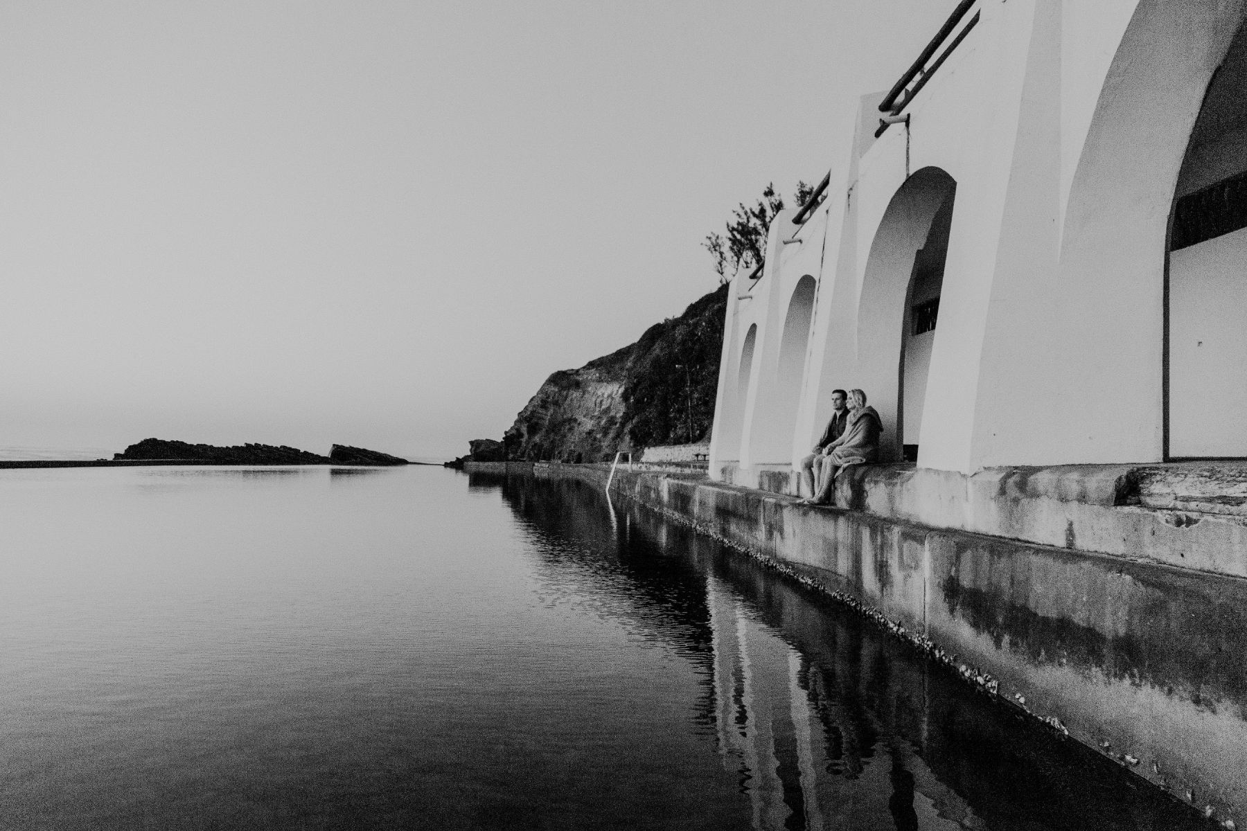 Architectural black and white image of intimate couple sitting together whilst looking over dark body of water