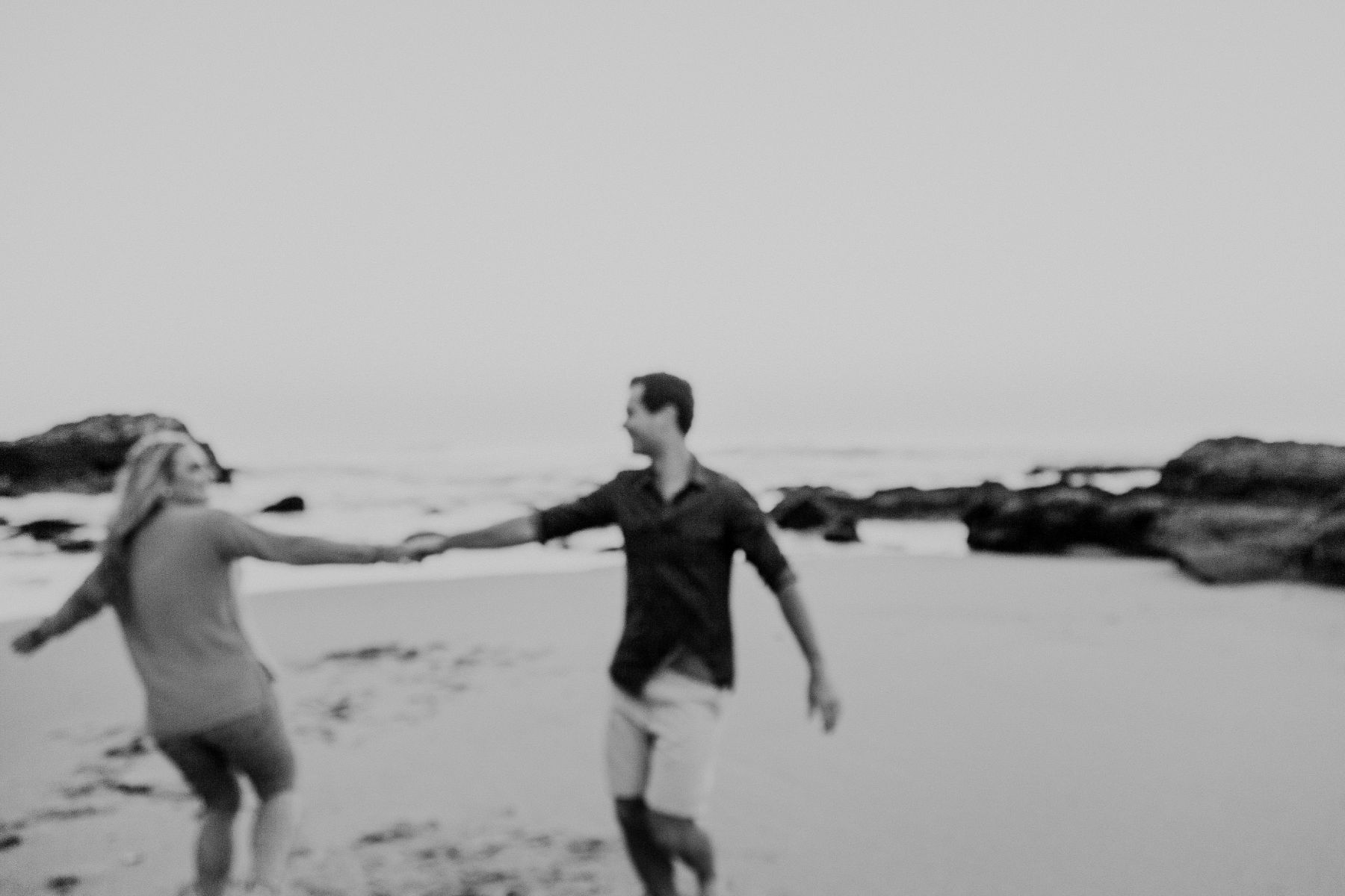 creative blurry black and white portfolio image of Durban couple holding hands and playing on the beach together