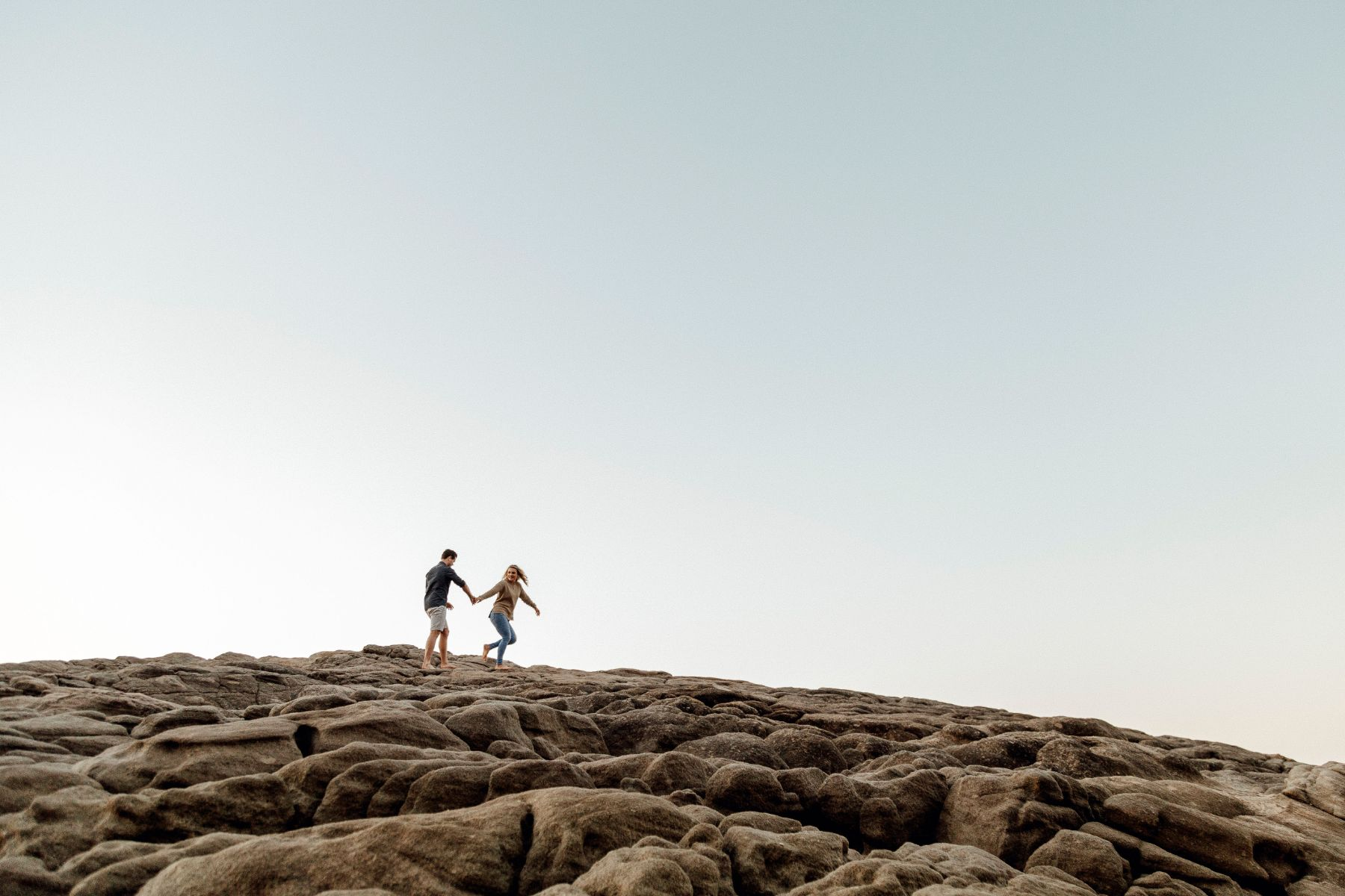 Minimal photo of modern girl leading fiancé but the hand across interesting rocks
