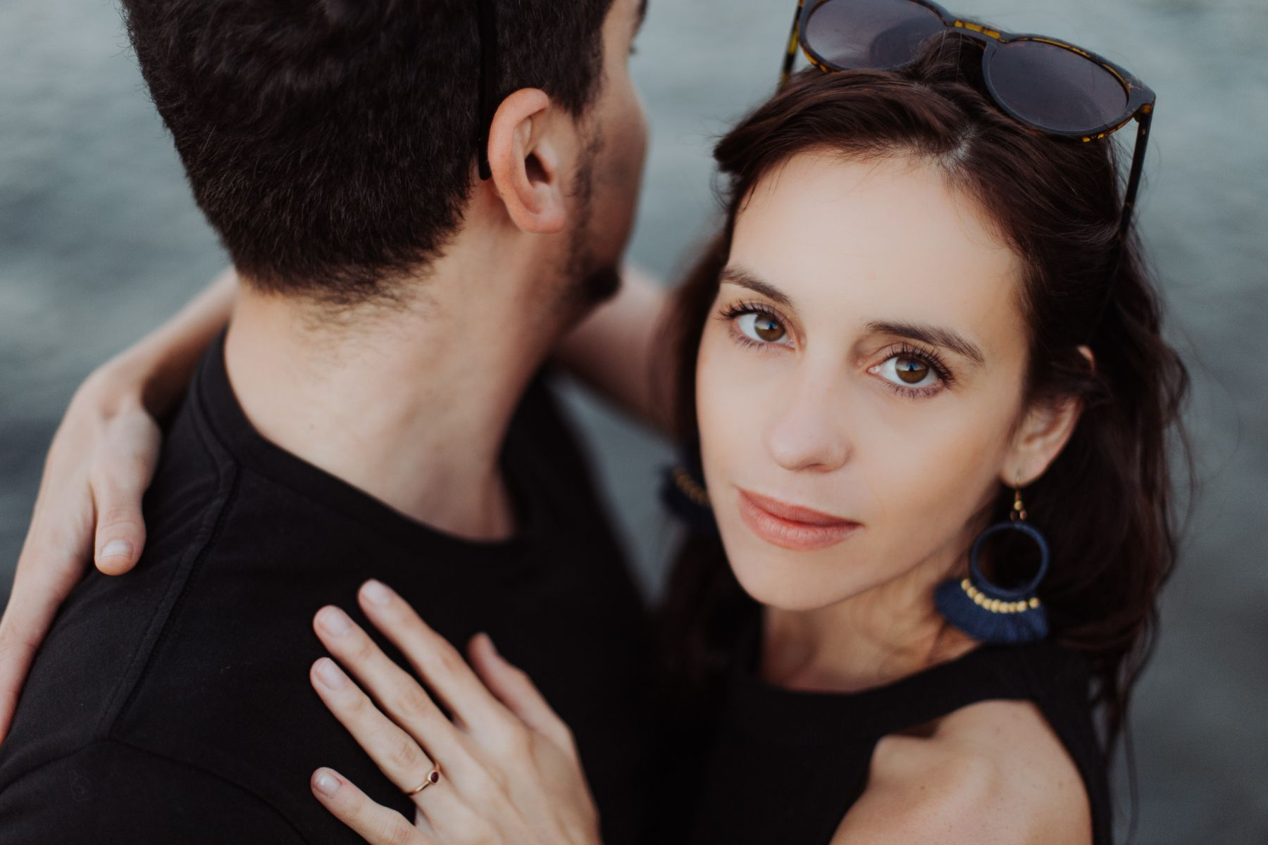 Editorial style engagement photo fo couple in black, man looks away whilst woman stares directly into the camera