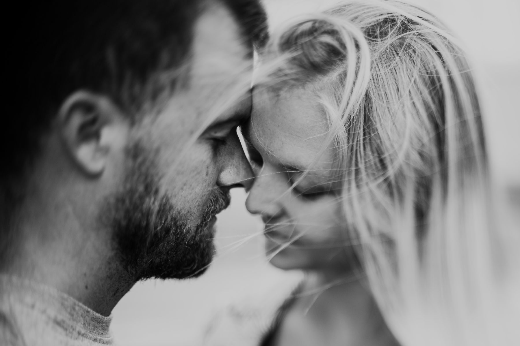Freelensed black and white portfolio image of couple intimately touching noses whilst hair blows freely in the wind