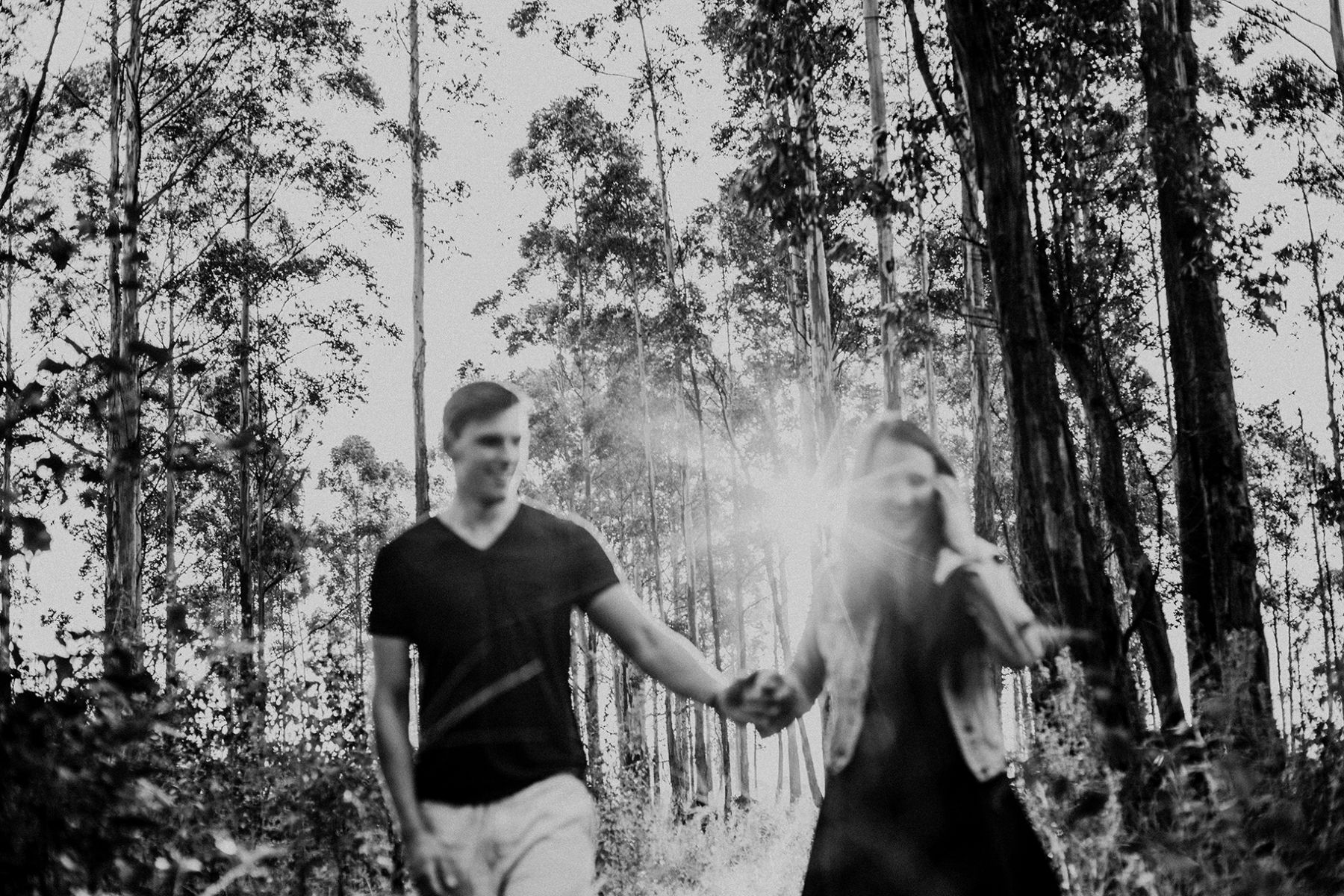 artistic and natural image of happy couple walking hand in hand in forest under late afternoon sunlight