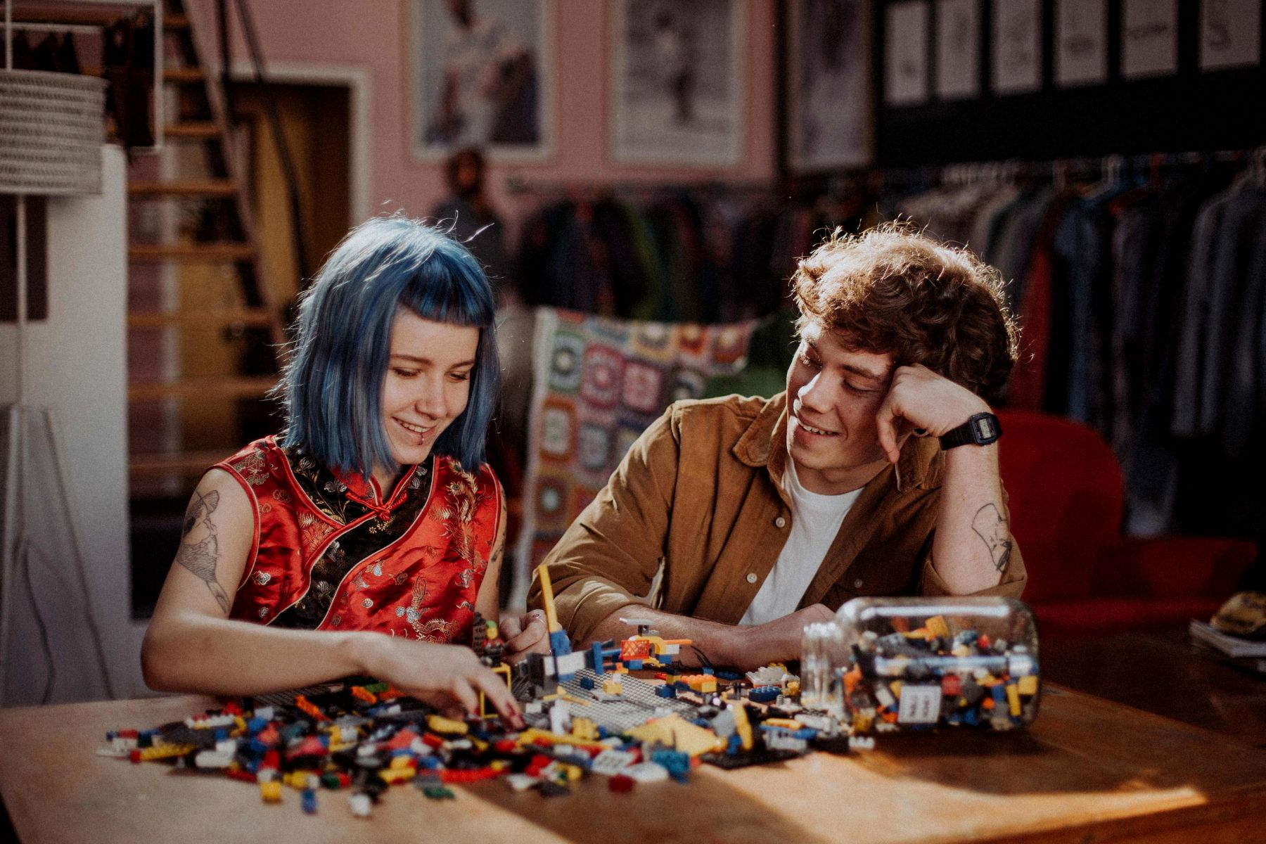 Couples portfolio image of artistic couple smiling and building lego together under beautiful natural light