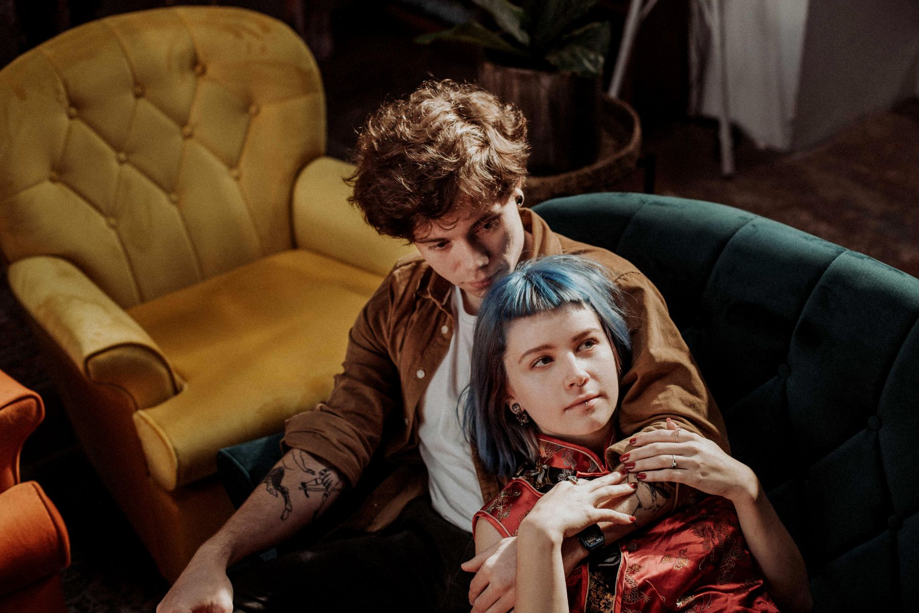 Modern couple sitting together on trendy turquoise couch, embracing in artistic cafe for couple portfolio