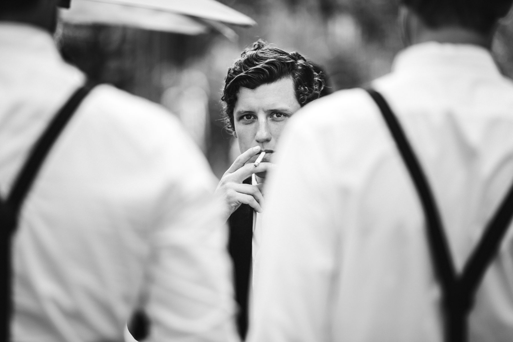 Vintage style documentary photo of stylish groom smoking cigarette whilst staring pensively