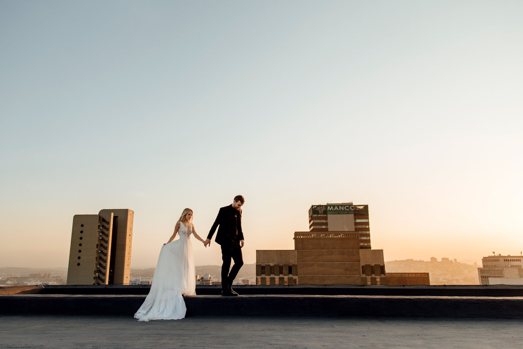 Editorial style wedding portfolio image of couple walking hand-in-hand on top of Durban rooftop with sunset in the background, wearing Hanrie Lues gown