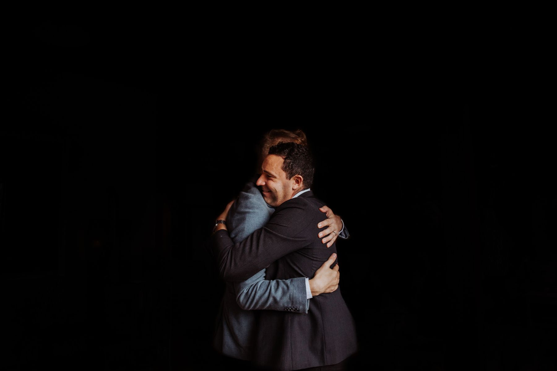 Striking documentary-style wedding portfolio image of two suited men embracing with dark background