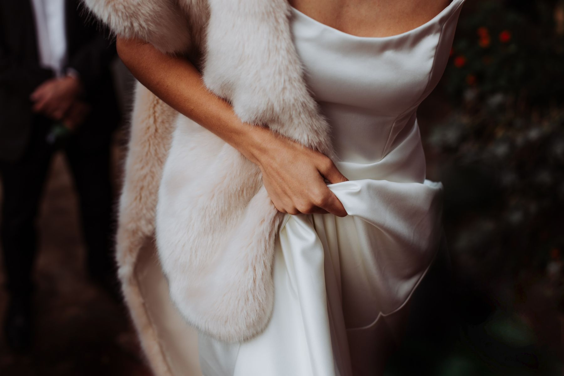 Editorial wedding portfolio image of bride walking whilst holding elegant, classical Sadie Bosworth wedding gown with fur shawl over shoulder