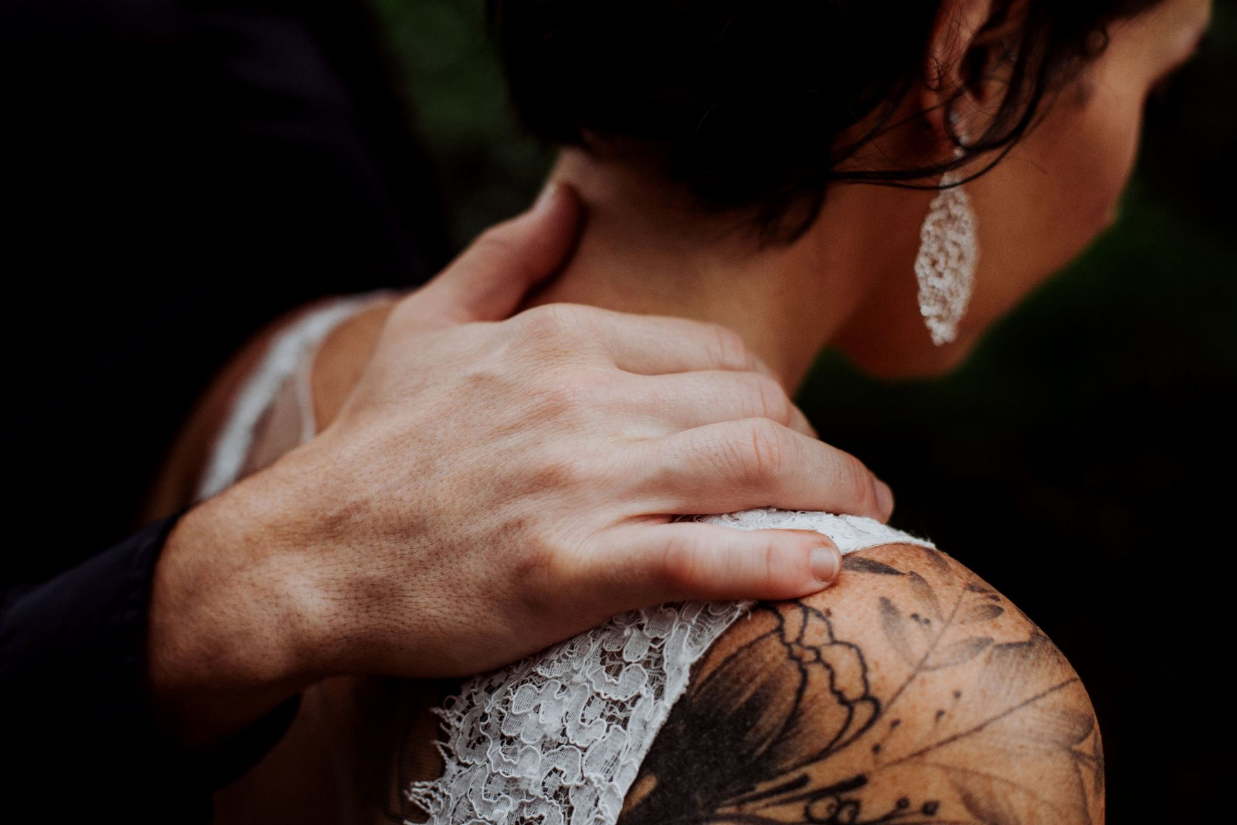 Wedding portfolio image of alternative bride with tattoos walking as groom places hand gently on her shoulder