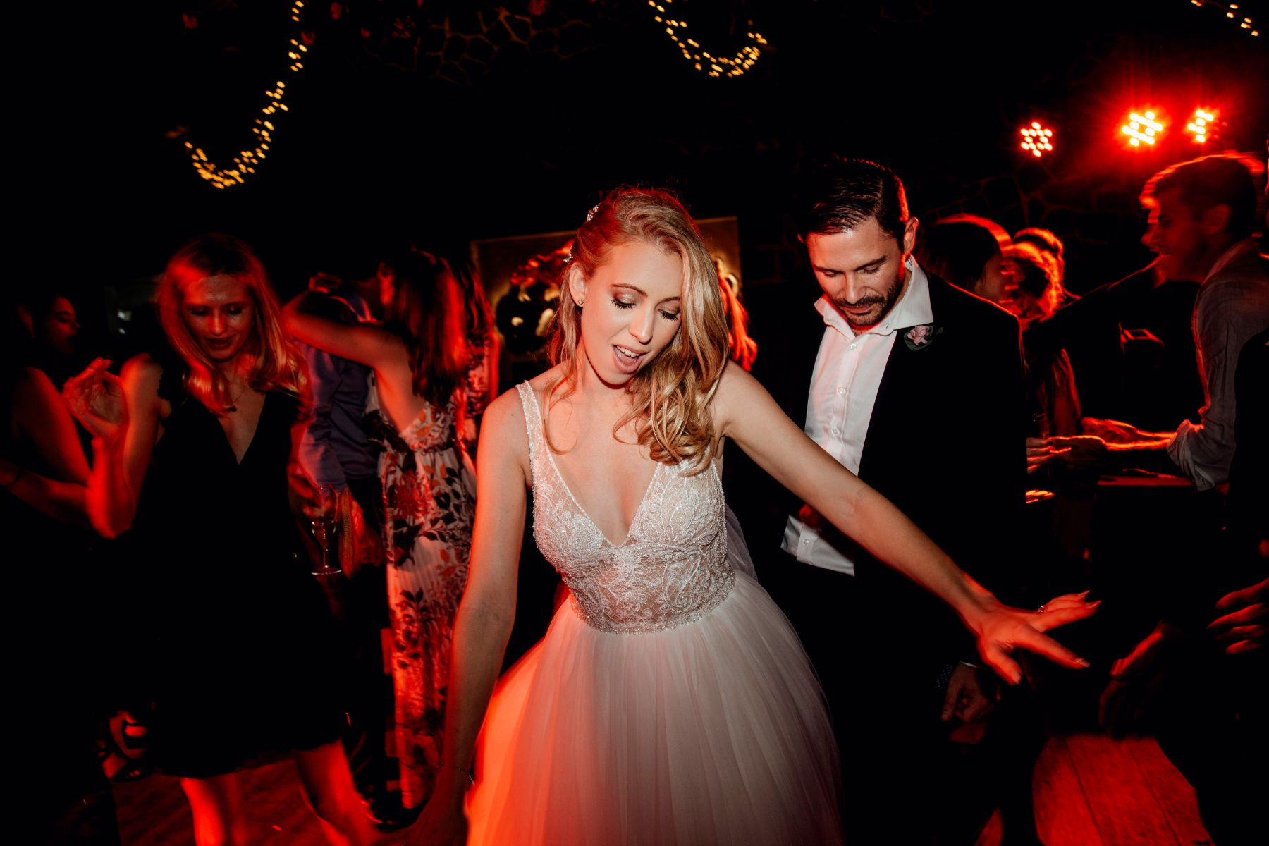 Fearless, modern bride dancing with groom at wedding whilst bathed in red dance floor lighting