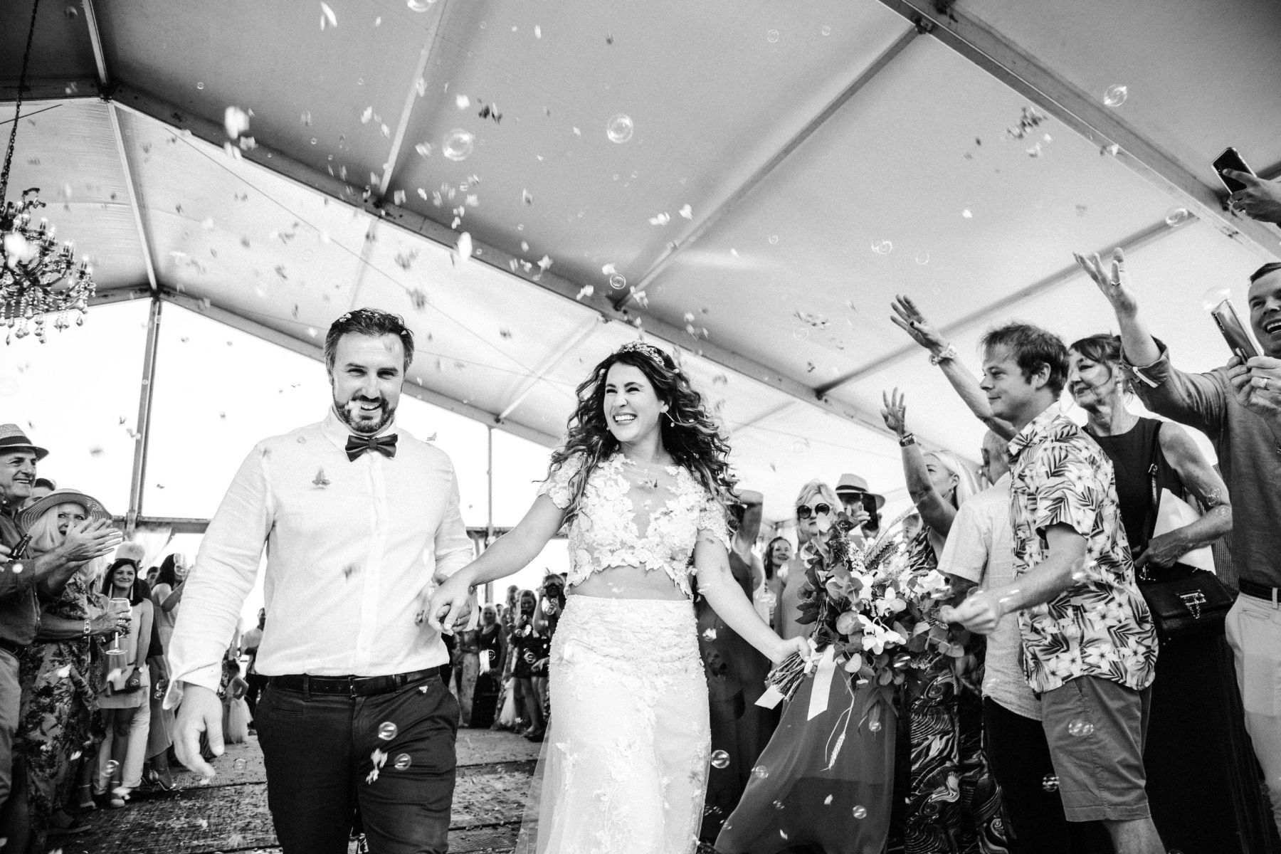 Wedding portfolio image of happy bohemian wedding couple surrounded by wedding guests throwing confetti in celebration, bride wears fashionable two piece wedding dress