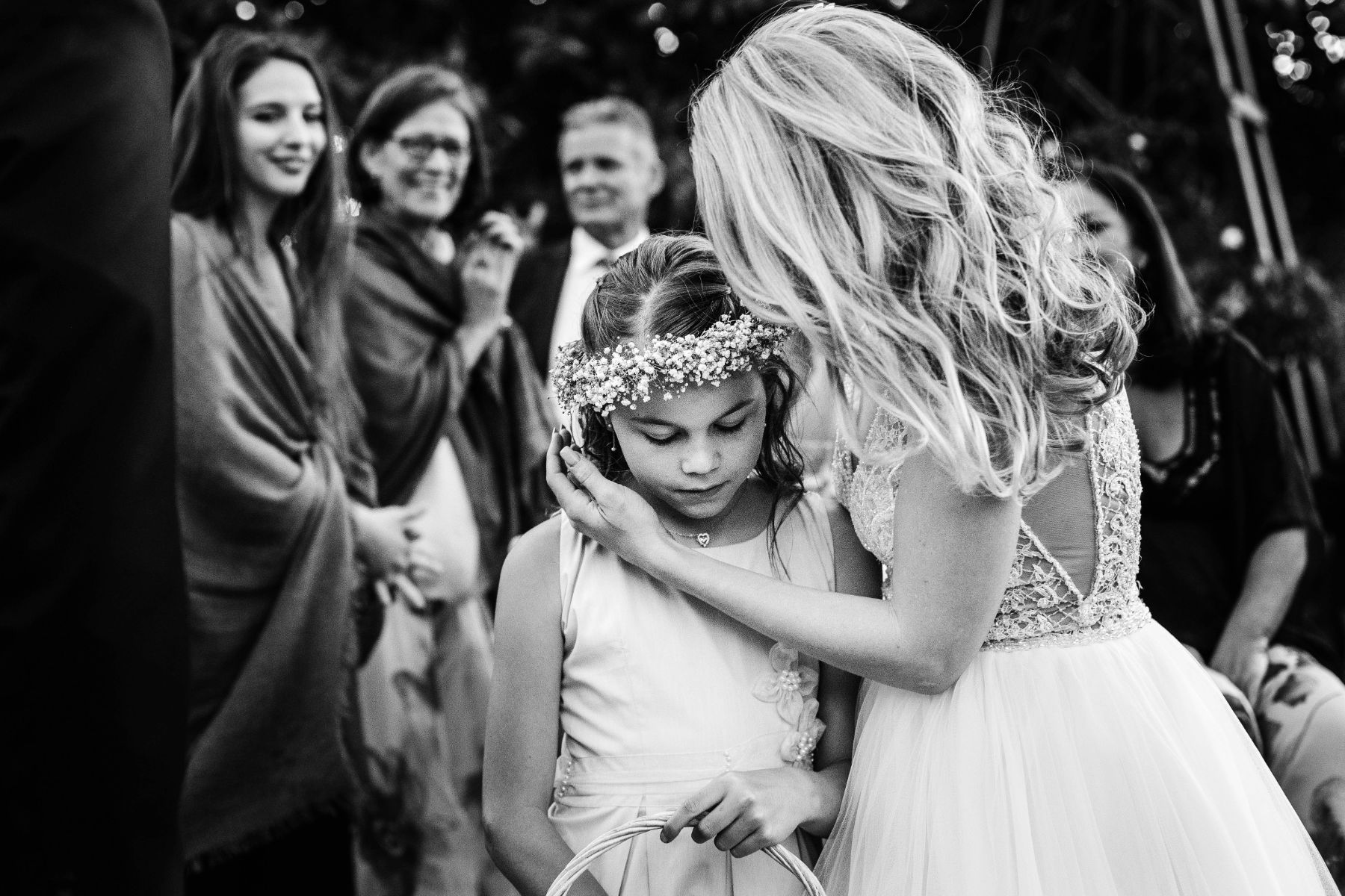 Documentary style black and white image of modern bride comforting young flower girl whilst wedding guests look on in admiration
