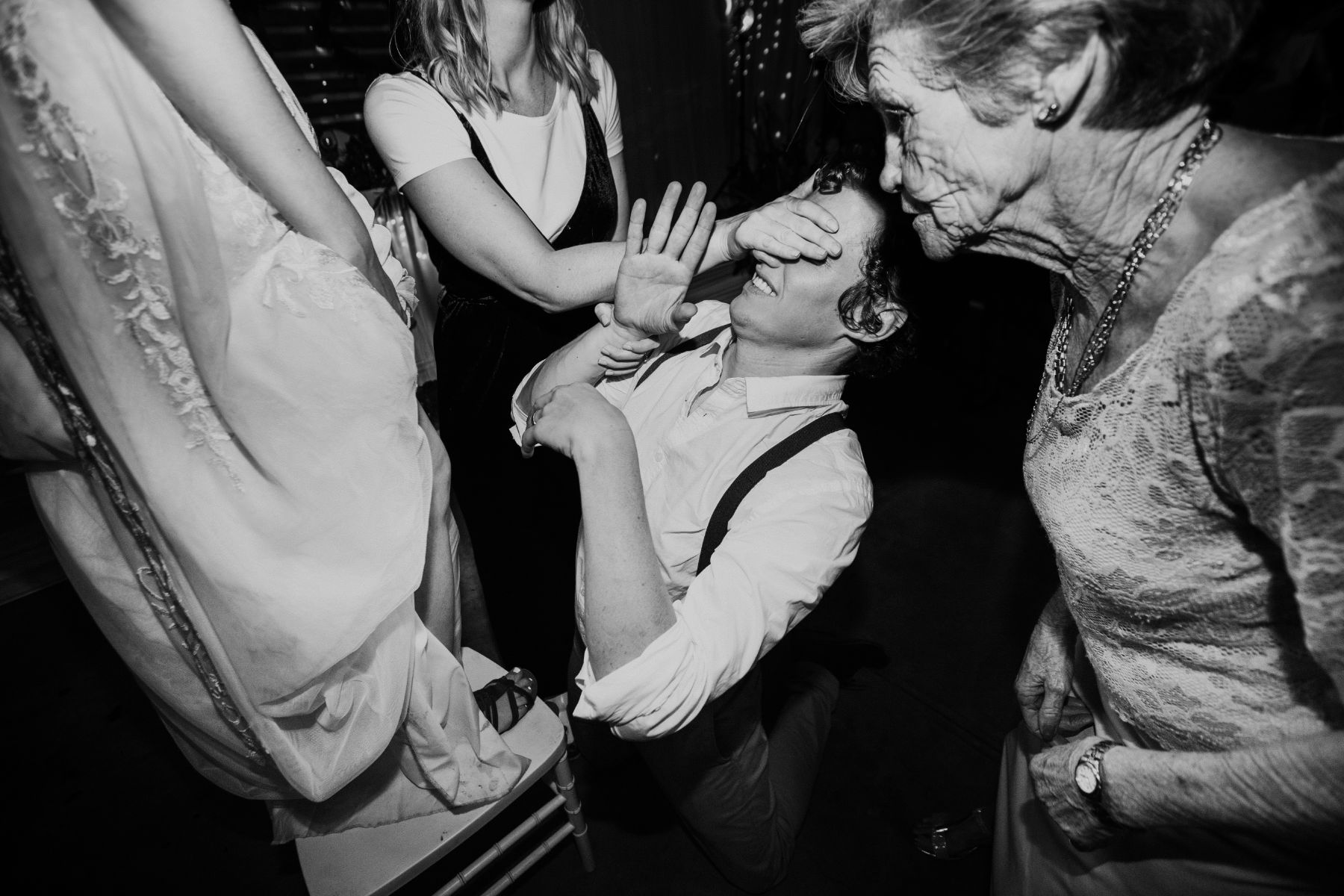 Documentary wedding photograph of groom about to receive wedding garter from bride as grandmother watches