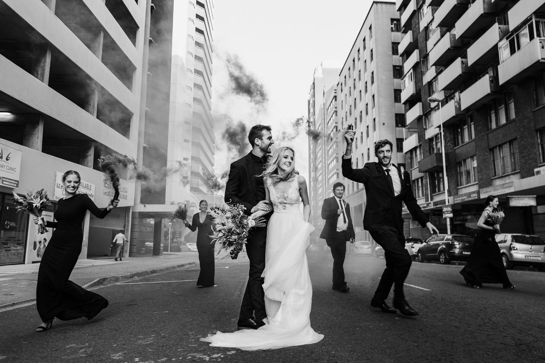Black and white documentary style image of bride and groom in city street whilst bridal party surround them with smoke bombs