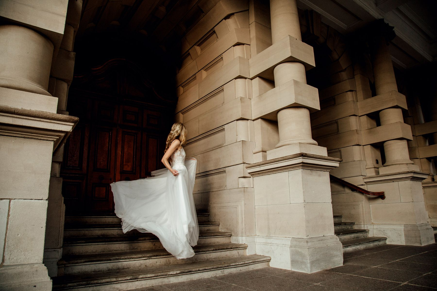 Wedding portfolio image of bohemian bride twirling down stairs of Durban City Hall with Hanrie Lues tulle dress flowing in the wind