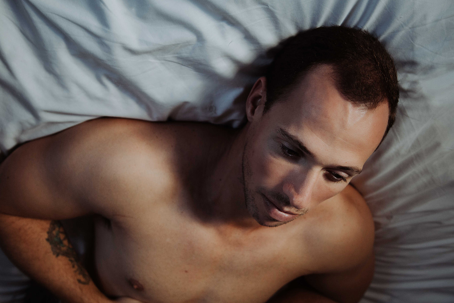 Fine art portrait of melancholic man lying in bed with soft window light