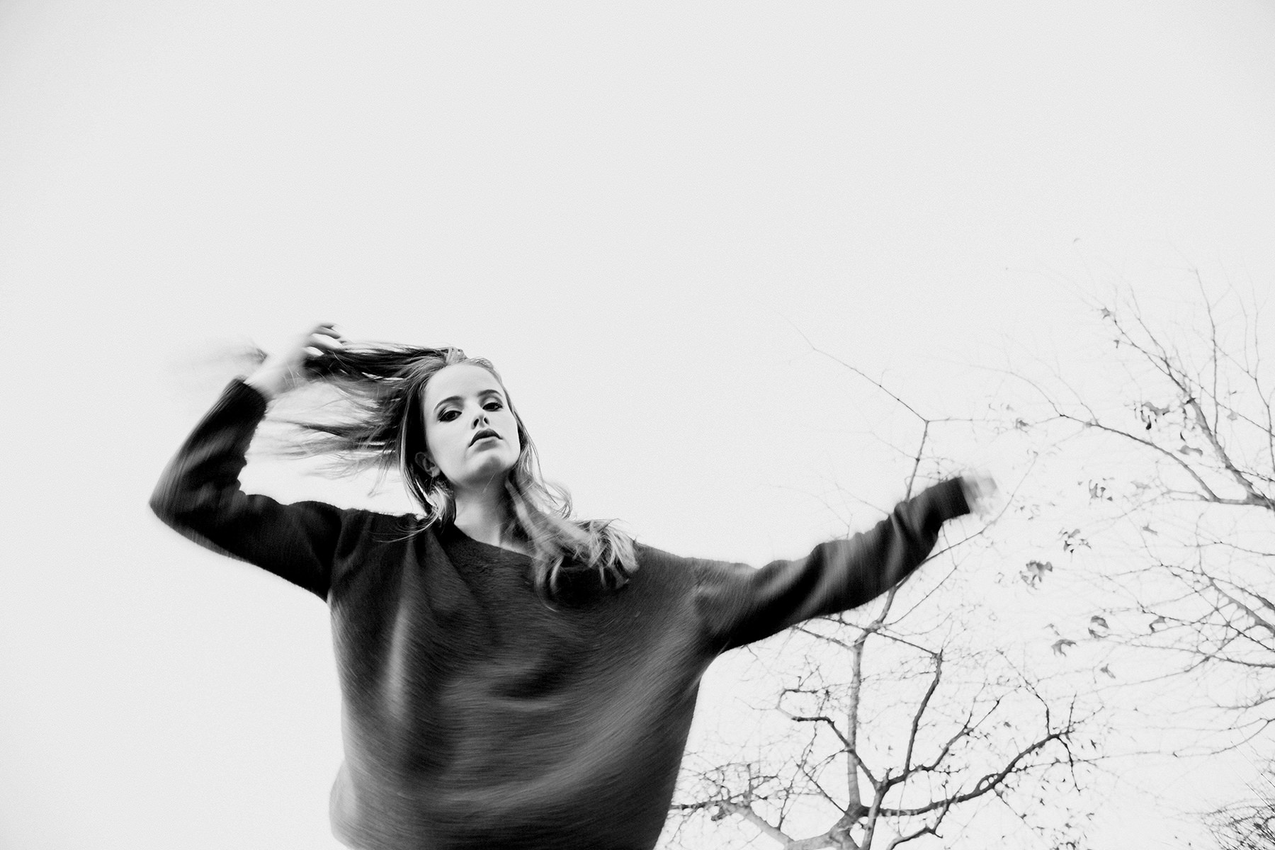 Blurry photo of beautiful female model swishing her hair and arms whilst staring down at camera in front of dry winter trees.