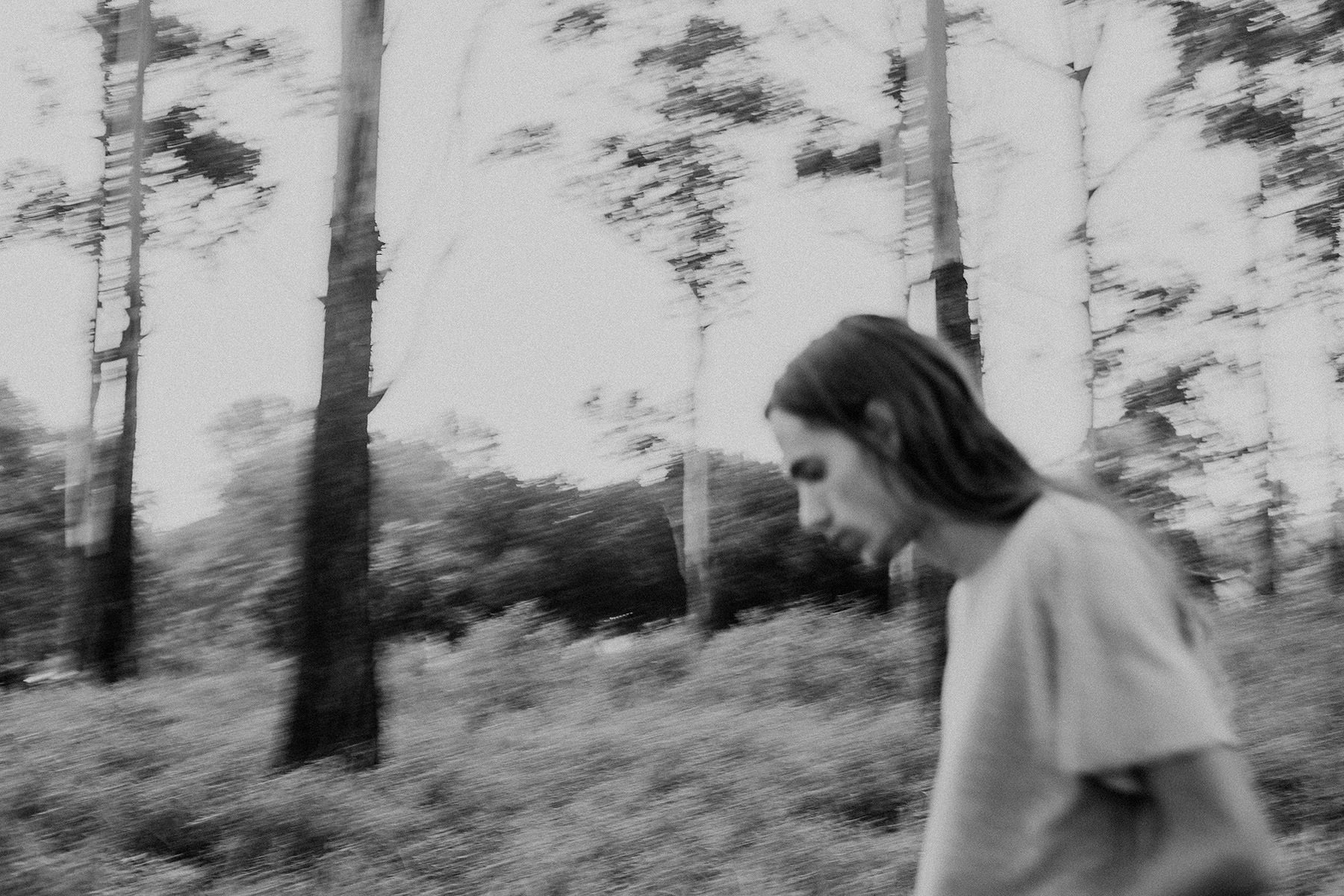Blurry black and white image of hippy man with long hair walking through a forest