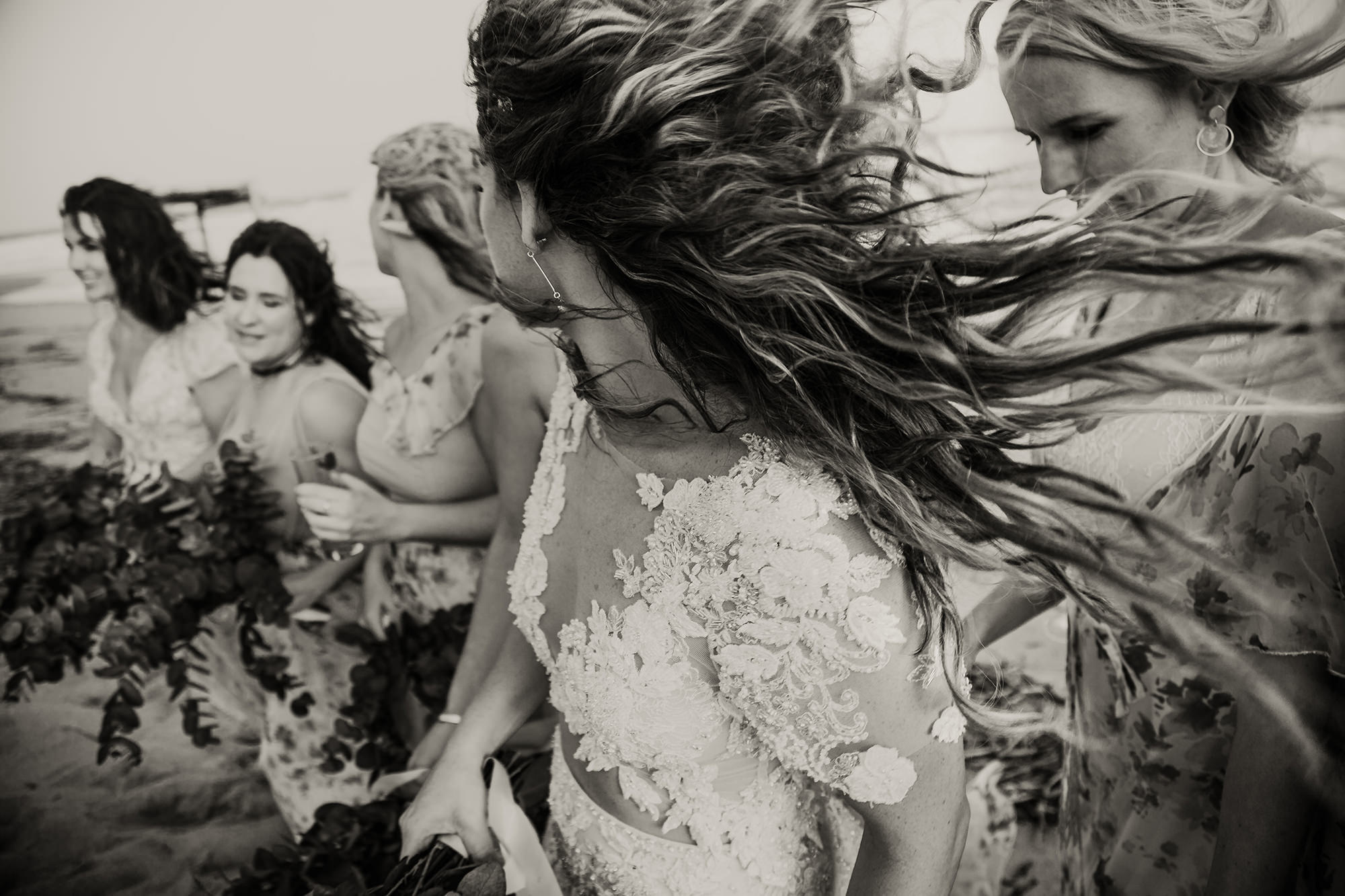 Bohemian bride in two piece wedding dress with bridesmaids on the beach, wind blowing through their hair